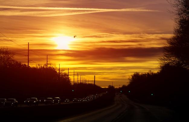 Autostrada z samochodem po zmierzchu błyszczy światło reflektorów samochodów pomarańczowego niebo