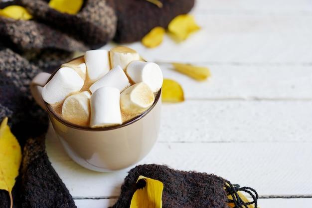 Autumn flatlay z filiżanką kawy, szalikiem, żółtymi liśćmi na białym drewnie