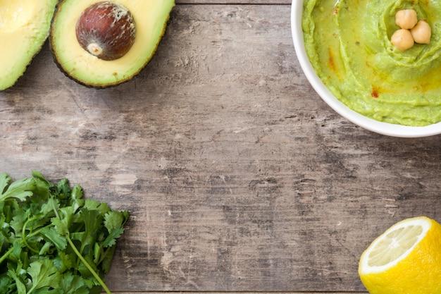 Avocado hummus w pucharu odgórnego widoku kopii drewnianej stołowej przestrzeni