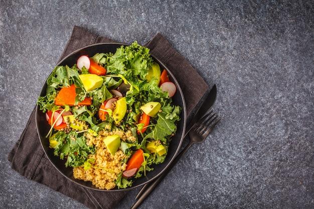 Avocado, quinoa, ignam i kale sałatka w czarnym talerzu na ciemnym tle.