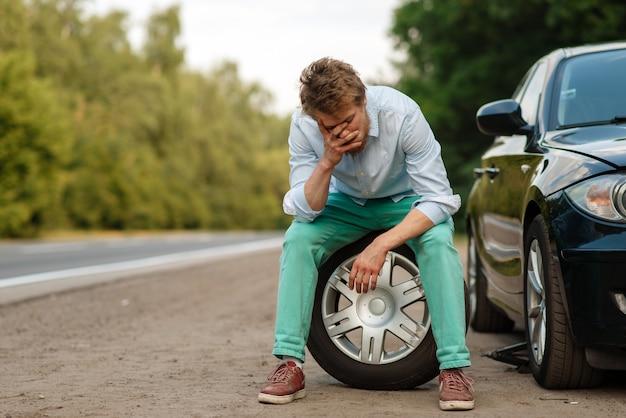 Awaria samochodu, zmęczony mężczyzna siedzi na zapasowej oponie