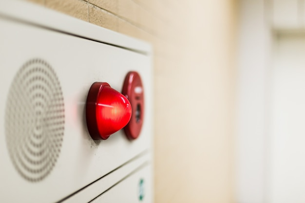 Awaryjne światło panelu ściennego i dźwięk głośnika alarmu w budynku biurowym.