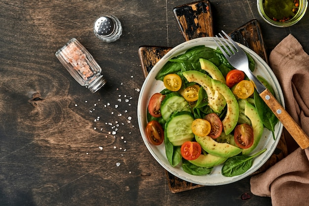 Awokado, czerwony, żółty, czarny pomidor koktajlowy, szpinak i ogórek świeża sałatka z przyprawami pieprzem i oliwą z oliwek w szarej misce stary drewniany stół tło. koncepcja zdrowej żywności. widok z góry.