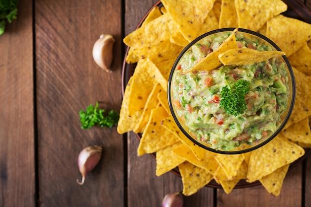 Awokado guacamole, limonka, pomidor, cebula i kolendra, podawane z nachos - tradycyjna meksykańska przekąska