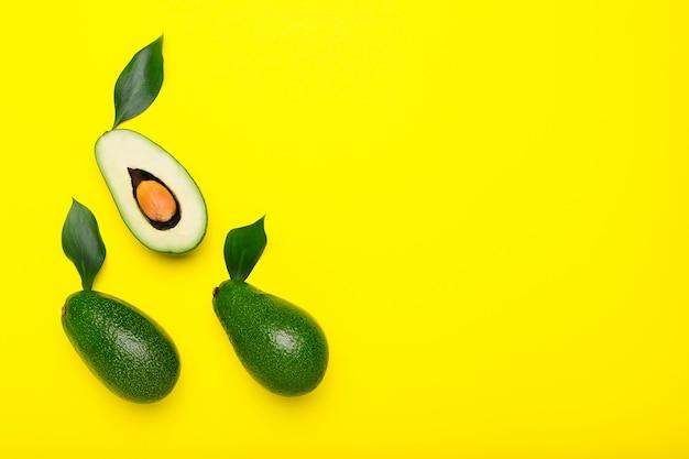 Awokado i połówki z liściem na kolor żółty widok z góry koncepcja letniego jedzenia