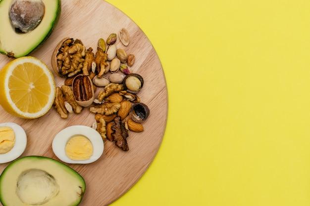 Awokado, jajka, cytryna, orzechy na drewnianej desce do krojenia. dieta ketogeniczna o płaskich układach.