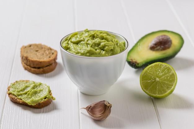 Awokado, limonka, chleb i czosnek z miską guacamole na białym stole. dieta wegetariańska meksykańskie jedzenie awokado. surowe jedzenie.