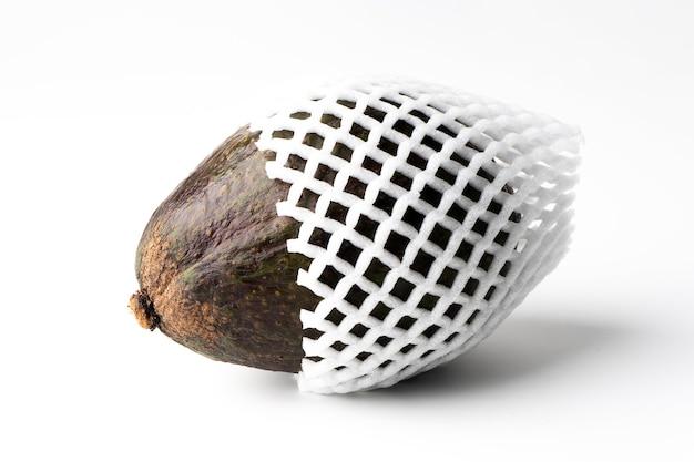 Awokado na owiniętej piankowej siateczce na białym tle, miąższ awokado jest kremowy i miękki o maślanym smaku. awokado zawiera składniki odżywcze, witaminy i dobre tłuszcze.