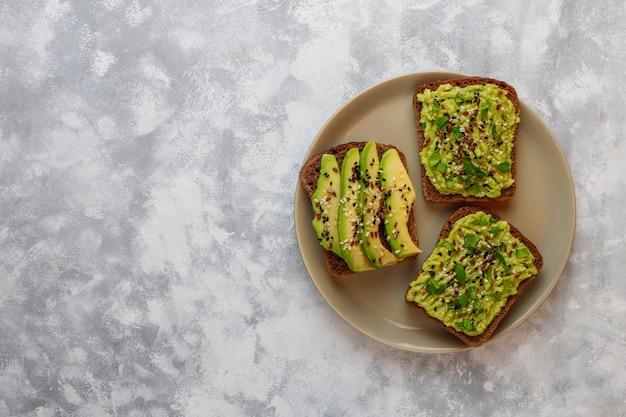 Awokado otwarte tosty z kawałkami awokado, cytryną, lnem, sezamem, kromkami czarnego chleba, widok z góry