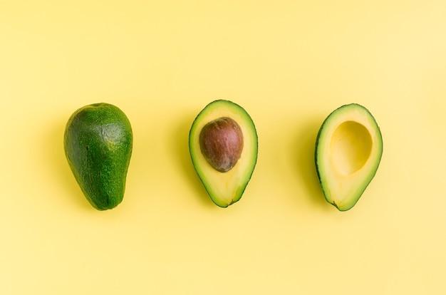 Awokado płaskie leżało na żółtym tle. prosta i minimalistyczna koncepcja. organiczna zdrowa żywność. widok z góry.