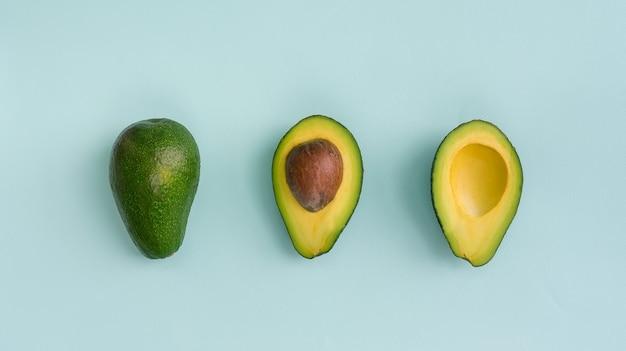 Awokado płasko leżało na niebieskim tle. prosta i minimalistyczna koncepcja. organiczna zdrowa żywność. widok z góry.