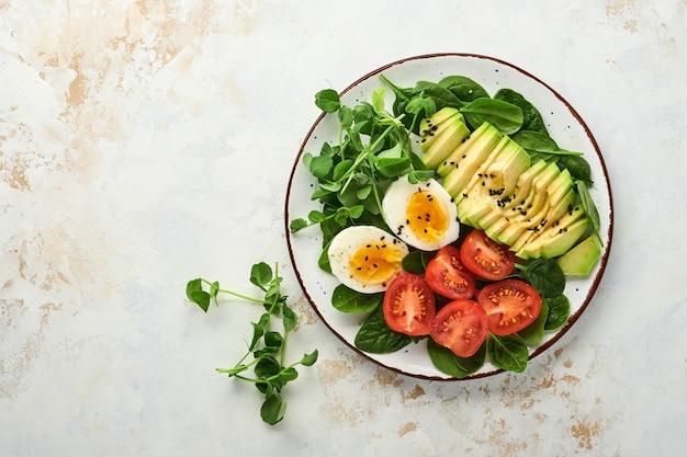 Awokado, pomidor koktajlowy, szpinak i jajko kurze, groszek microgreens i świeża sałatka z czarnego sezamu w misce na tle białego stołu z kamienia. koncepcja żywności zdrowe śniadanie. widok z góry.