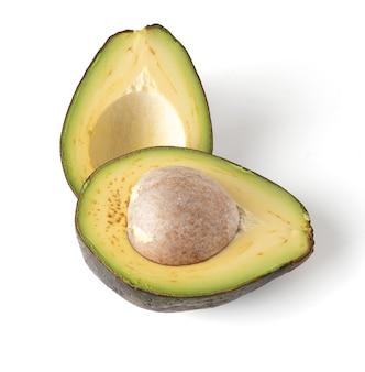 Awokado przekrojone na pół na białym tle, miąższ awokado jest kremowy i miękki o maślanym smaku. awokado zawiera składniki odżywcze, witaminy i dobre tłuszcze.