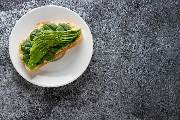 Awokado toast z humusem na ciemnym tle betonu. jedzenie wegetariańskie. widok z góry. skopiuj miejsce