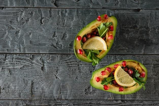 Awokado z pestkami granatu, sosem balsamicznym, cytryną i natką pietruszki na rustykalnym stole. kuchnia wegetariańska na odchudzanie. widok z góry.