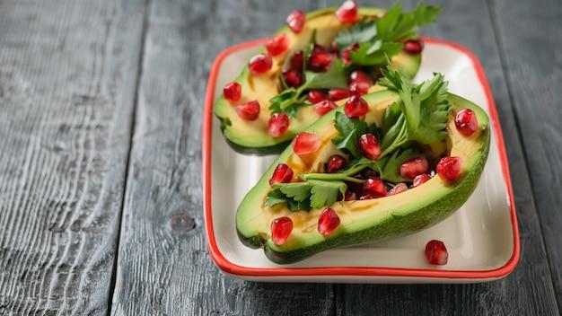 Awokado z pestkami granatu, sosem balsamicznym i cytryną na biało-czerwonej misce. kuchnia wegetariańska na odchudzanie.
