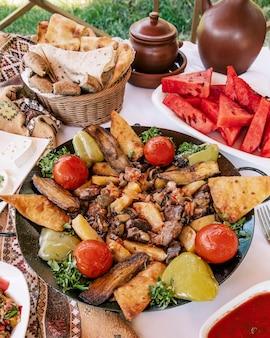 Azerbaijani sac ichi z mieszanymi składnikami, chlebem i arbuzem.