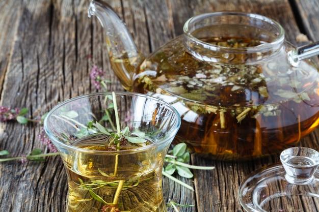 Azerbejdżańska czarna herbata z świeżą macierzanką w wschodnim szkle i szklany czajniczek, rocznika drewniany tło