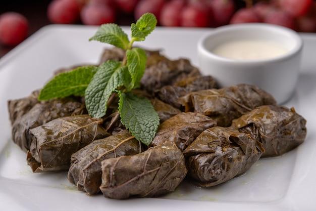 Azerbejdżańska dolma w liściach winogron na białym talerzu