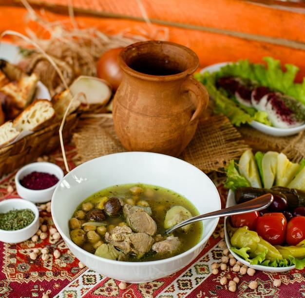 Azerbejdżański gulasz z misy bozbash podawany z marynatami i chlebem
