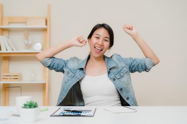 Azja biznes kobieta sukces uroczystości trzymając ręce podniesione w domowym biurze.