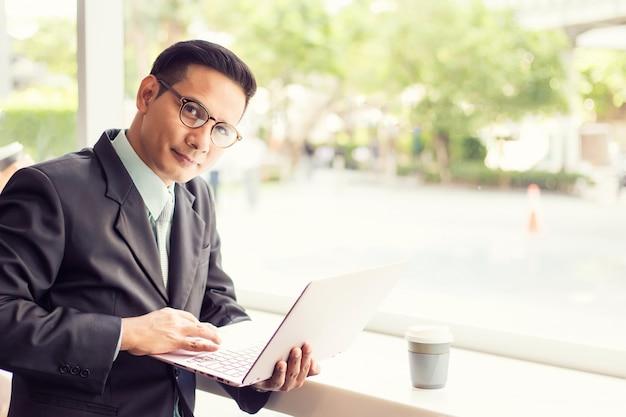 Azja biznesowy mężczyzna pracuje z laptopem podczas gdy siedzący sklep z kawą