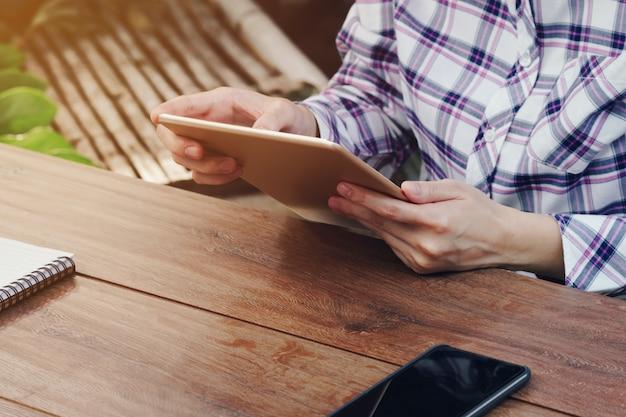 Azja kobieta używa pastylkę na stole w sklep z kawą