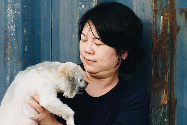 Azja kobiety i psi szczęśliwy przytulenie z zbiornikiem