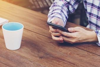 Azja kobiety ręka trzyma telefon i używa w sklep z kawą.