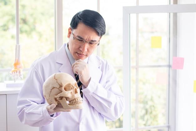 Azja lekarki mężczyzna mienia czaszki poważna twarz myśleć o pytaniu.