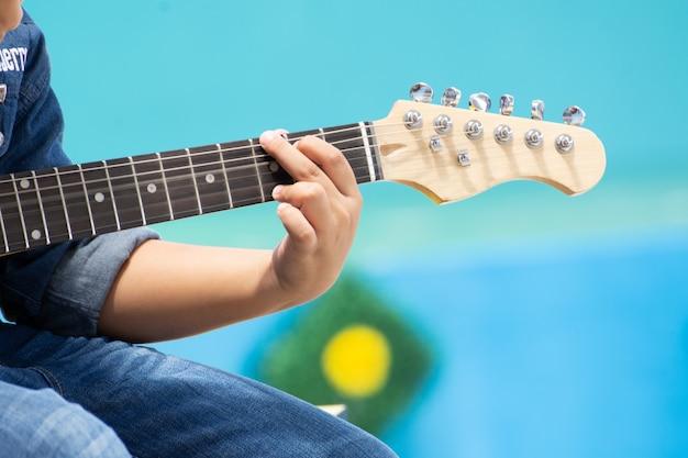 Azja młoda chłopiec bawić się gitarę