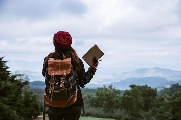 Azja młoda kobieta trzyma notatnika na szczytowym góry doi inthanon przy chiangmai, tajlandia
