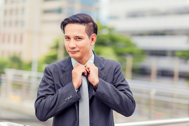 Azja młody biznesowy mężczyzna przed nowożytnym budynkiem w śródmieściu