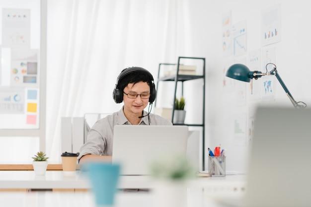 Azja przedsiębiorca dystans społeczny w nowej normalnej sytuacji w celu zapobiegania wirusom za pomocą prezentacji laptopa do kolegi o planie w rozmowie wideo podczas pracy w biurze domowym. styl życia po wirusie koronowym.