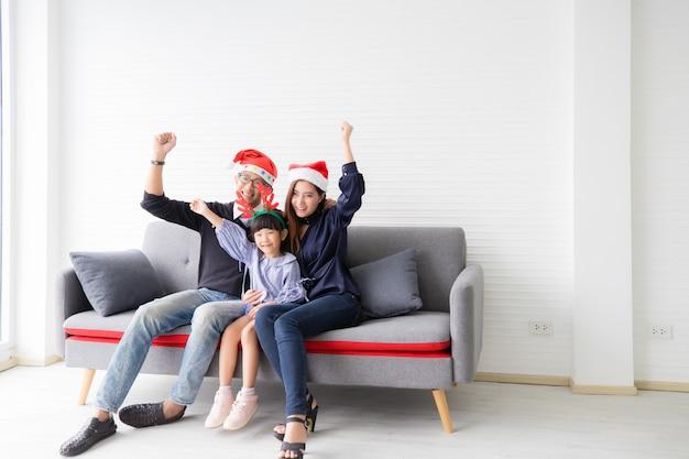 Azjaci azjatyccy rodzice i dzieci podnoszą ręce i siedzą rano na kanapie w salonie w domu. mają uśmiechniętą i szczęśliwą twarz. pojęcie dopingowania do zwycięstwa