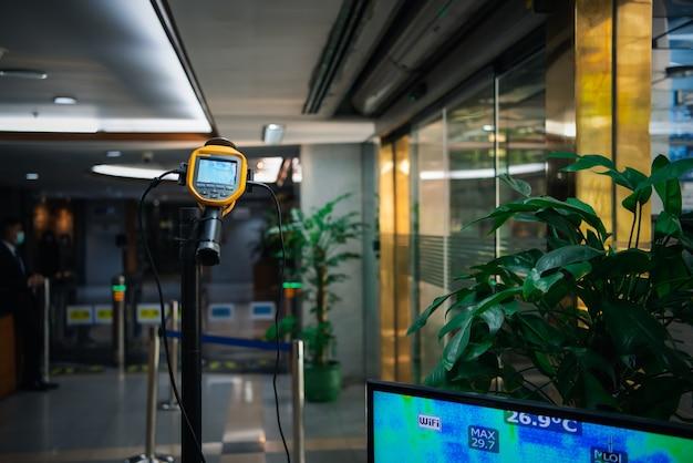 Azjaci czekają na kontrolę temperatury ciała przed wejściem do budynku pod kątem epidemii grypy covid19 lub grypy koronowej w biurze za pomocą termoskopu lub kamery termowizyjnej na podczerwień