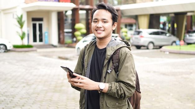 Azjaci noszą plecaki, trzymając telefon komórkowy