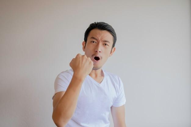 Azjaci w białych koszulkach unosząc pięść w prawą dłoń pokazują oznaki radości