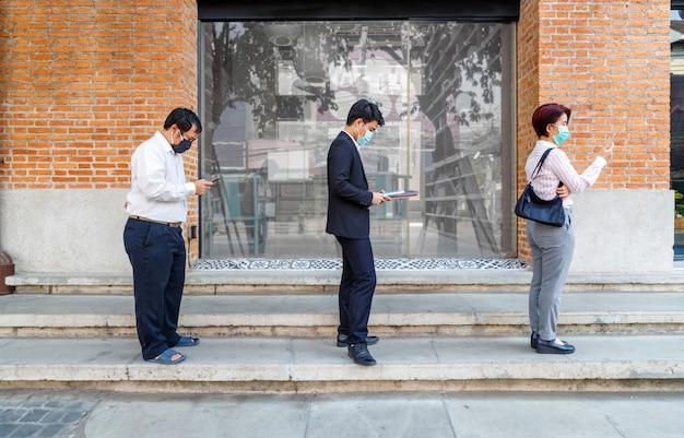 Azjaci w maskach i utrzymujący dystans społeczny, aby uniknąć rozprzestrzeniania się covid-19