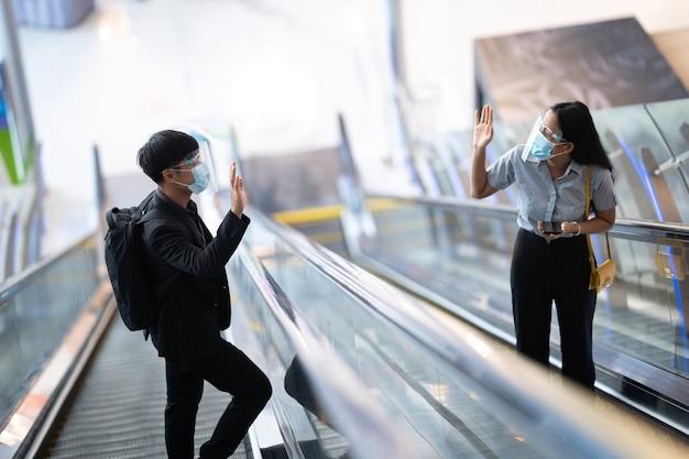 Azjaci witają się przy schodach ruchomych. z dystansem społecznym