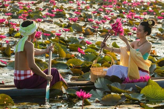 Azjaci zbierają czerwone kwiaty lotosu