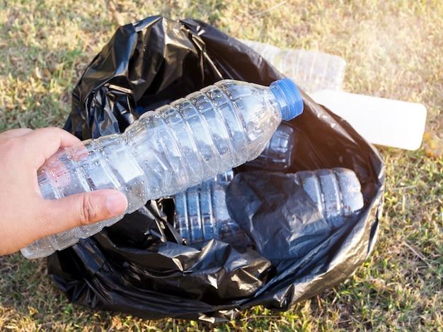 Azjaci zbierają śmieci plastikowymi butelkami z recyklingu w czarnym worku na śmieci. wolontariusze chronią środowisko, czyszcząc park i przyrodę.
