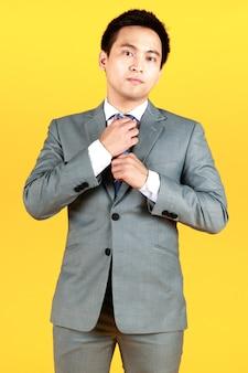 Azjata dobrze ubrany w szary garnitur i białą koszulę, stojący na żółtym tle. biznesmen krzyżując ramiona z silnym wyrazem twarzy.