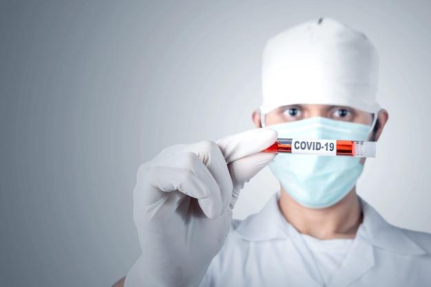 Azjata doktorski mężczyzna w grypowej masce i rękawiczkach ochronnych trzyma próbnej tubki z próbką krwi koronawirusa