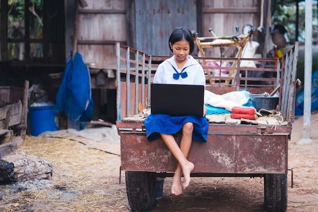 Azjata jednolitego ucznia dziewczyna używa komputerowego notatnika