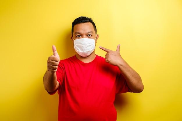 Azjata kciuk w górę i noszenie masek, aby zapobiec rozprzestrzenianiu się wirusa corona na żółtym tle