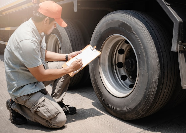 Azjata, kierowca ciężarówki trzymający notes, sprawdza bezpieczeństwo kół i opon ciężarówki.