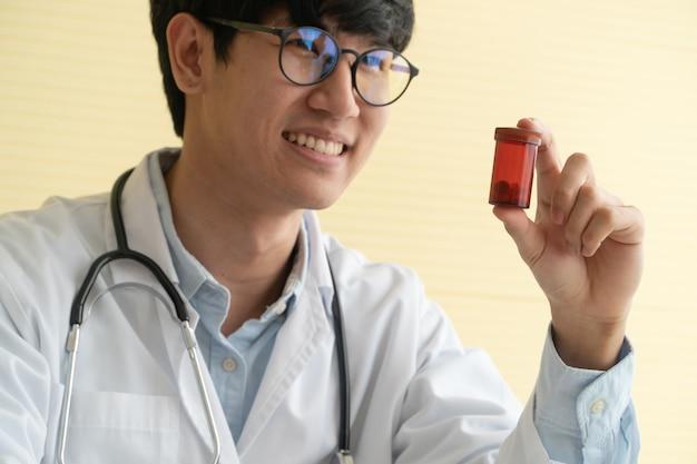 Azjata lekarka trzyma medycyny butelkę z stetoskopem i mundurem