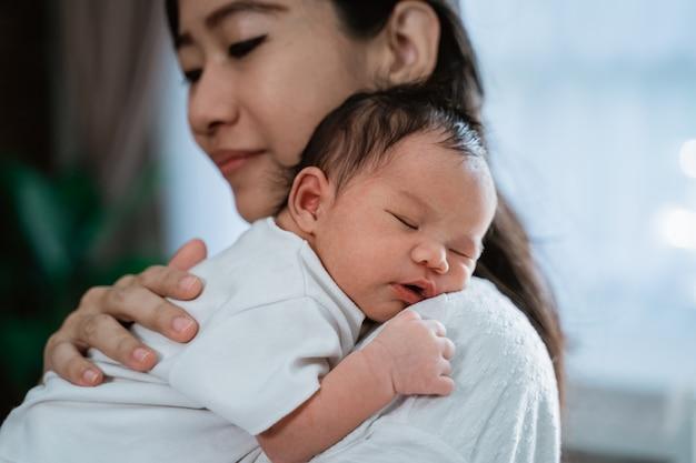 Azjata macierzysty uścisk niesie nowonarodzonej małej córki