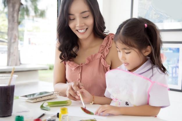 Azjata matka i córka maluje wodnego kolor